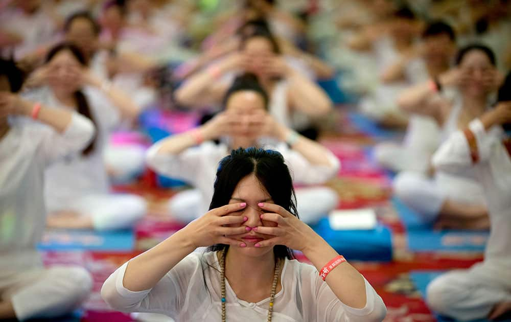 Chinese perform yoga under the instructions of Indian yoga teachers at a hotel banquet hall to mark the International Yoga Day, in Changping District, on the outskirts of Beijing, China.