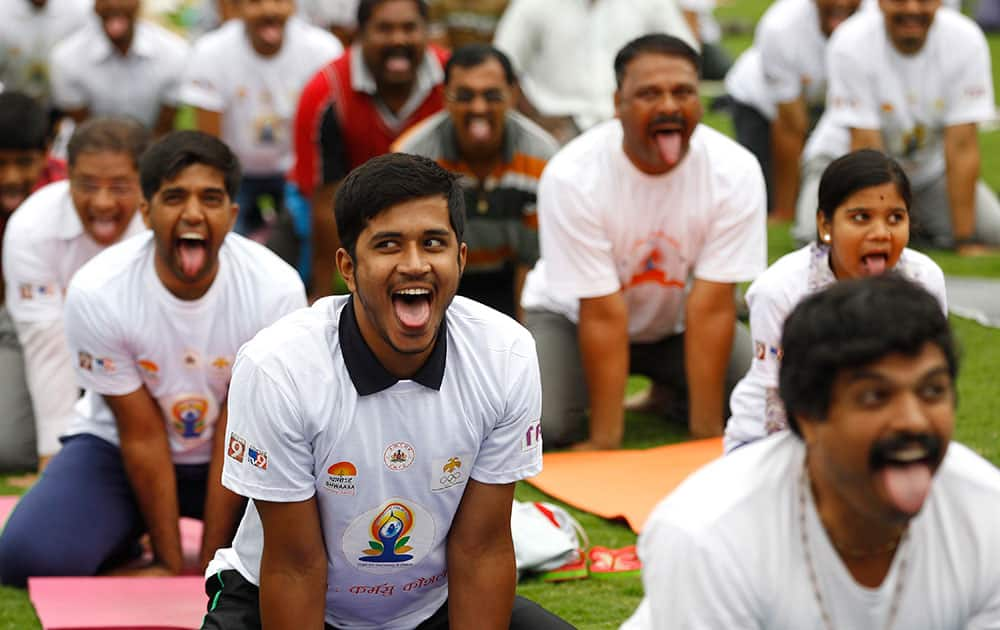 Indians perform yoga at an event to celebrate the International Yoga Day in Bangalore, India.
