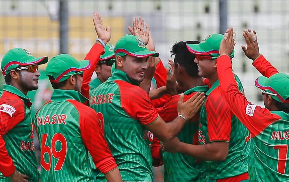 Bangladesh's players celebrate the dismissal of India's Rohit Sharma during their second one-day international cricket match in Dhaka, Bangladesh.