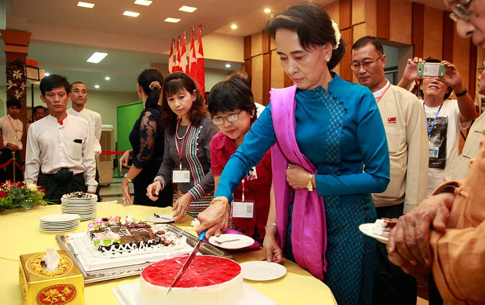 Myanmar opposition leader Aung San Suu Kyi cuts a cake during a ceremony to mark her 70th birthday anniversary organized by members of her National League for Democracy Party at Royal Rose restaurant in Yangon, Myanmar.
