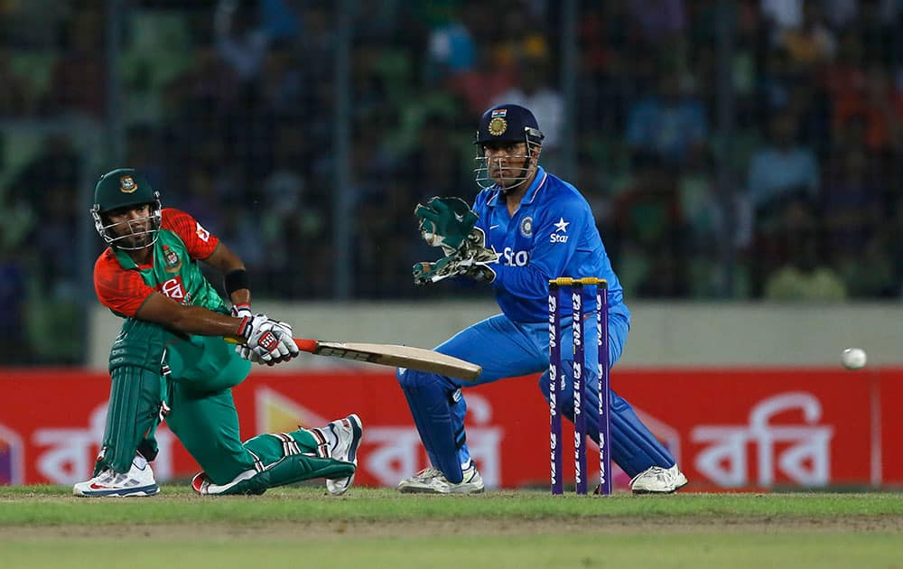 Bangladesh's Litton Das, left, plays a shot, as India's captain M S Dhoni watches during their second one-day international cricket match in Dhaka, Bangladesh.