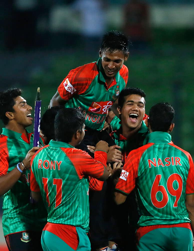 Bangladesh's players lift Mustafizur Rahman, center, as they celebrate their win over India during their second one-day international cricket match in Dhaka, Bangladesh.