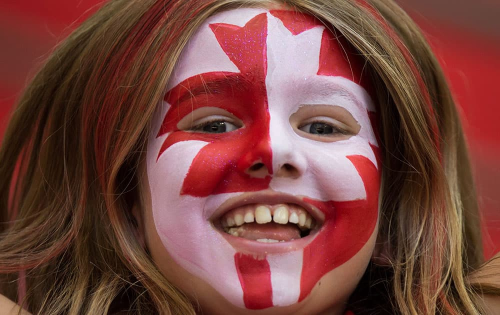 A young Canadian fan cheers as Canada and Switzerland warm up before a FIFA Women's World Cup round of 16 soccer game in Vancouver, British Columbia.