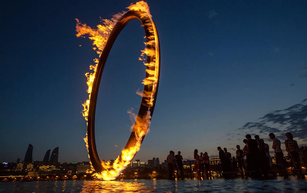 People walk near the giant ring with the flame of the 2015 European Games at the embankment of Caspian Sea in Baku, Azerbaijan.