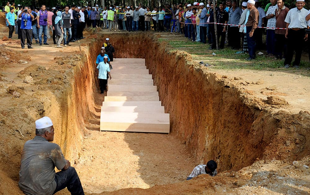 Malaysian religious officers and villagers place coffins containing remains of Rohingya migrants for a mass burial ceremony in Kedah, Malaysia .
