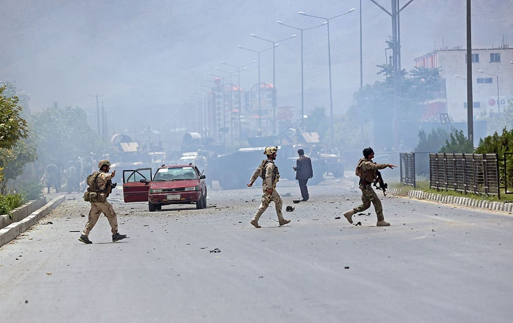 Afghan security forces run at the site of a suicide attack during clashes with Taliban fighters in front of the Parliament, in Kabul, Afghanistan.