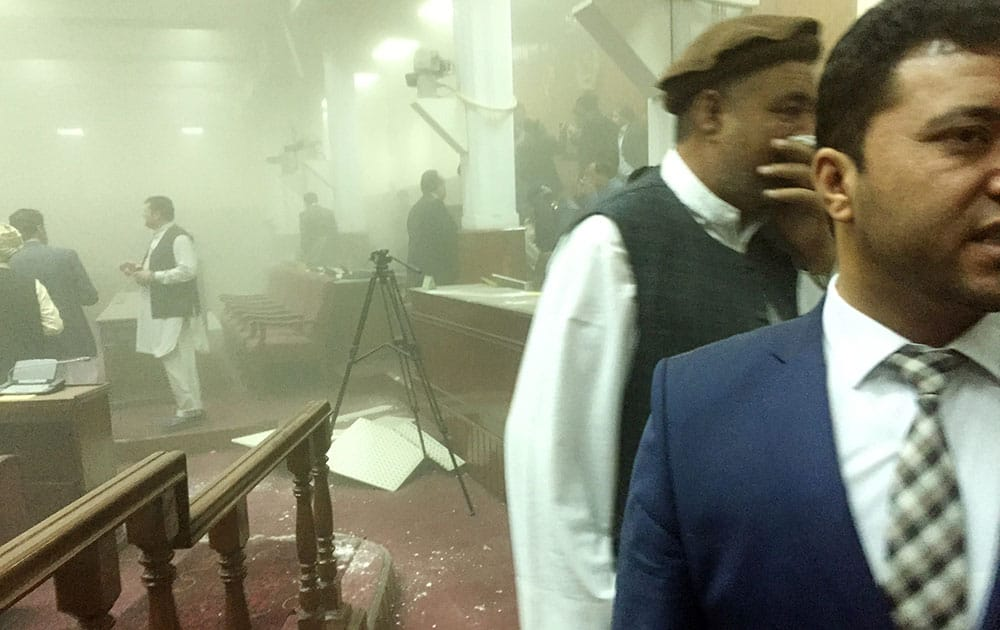 In this photo taken by Dr. Naqibullah Faiq, an Afghan member of parliament, lawmakers leave the main hall after a suicide attack in front of the main gate of Parliament, during clashes with Taliban fighters in Kabul, Afghanistan.