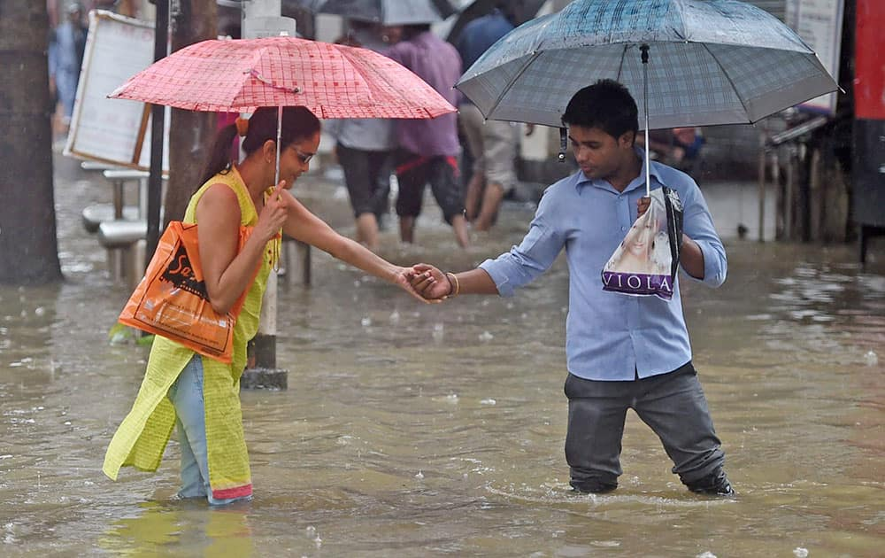 People wade through a water logged street after heavy downpour in Mumbai.