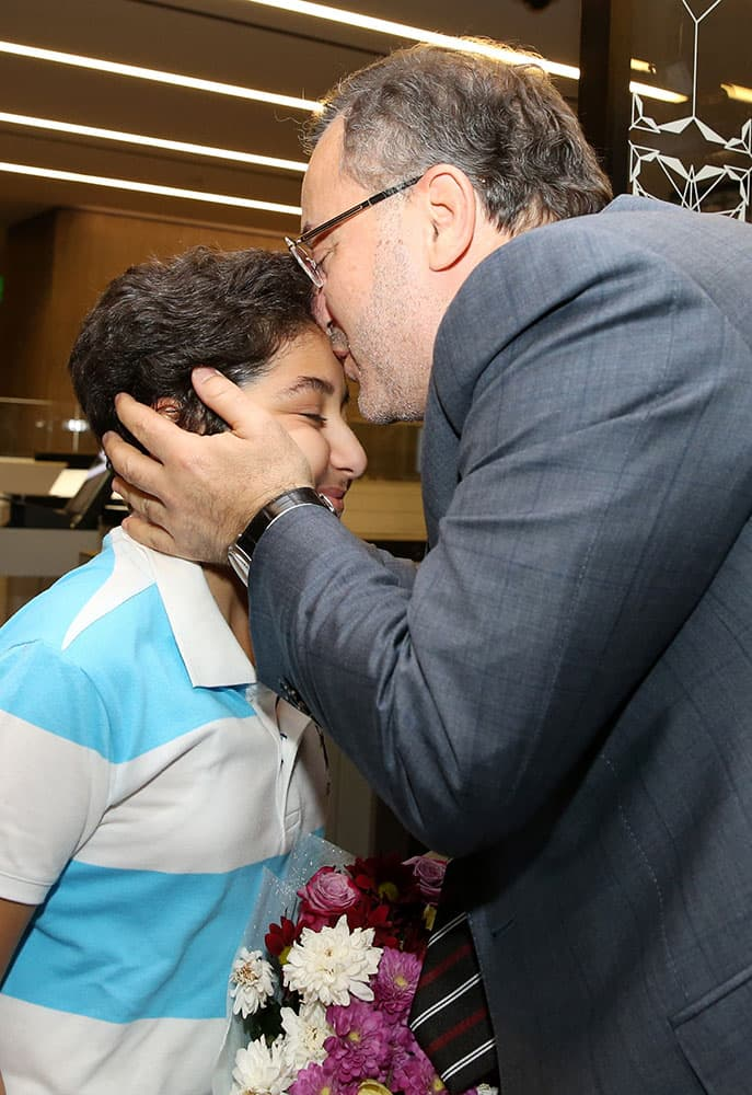 Al-Jazeera journalist Ahmed Mansour, right, kisses his son Mohammed after his arrival at Hamad airport in Doha, Qatar.