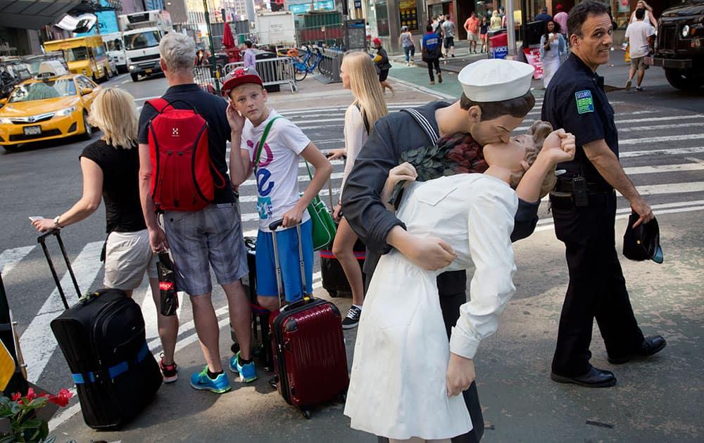 Pedestrians pass a sculpture of a sailor kissing a woman in New York.