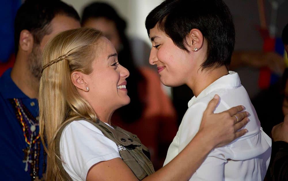 Lilian Tintori, wife of jailed opposition leader Leopoldo Lopez, left, embraces Patricia Ceballos, the wife of jailed opposition San Cristobal Mayor Manuel Ceballos, during a press conference in Caracas, Venezuela.