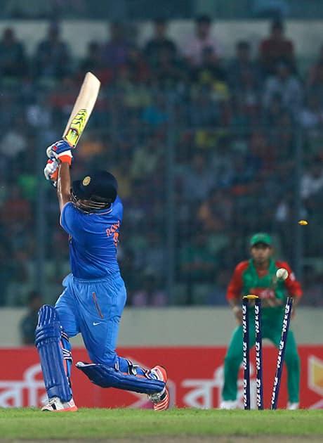 Suresh Raina is bowled out by Bangladesh's Mustafizur Rahman during their third one-day international cricket match in Dhaka.