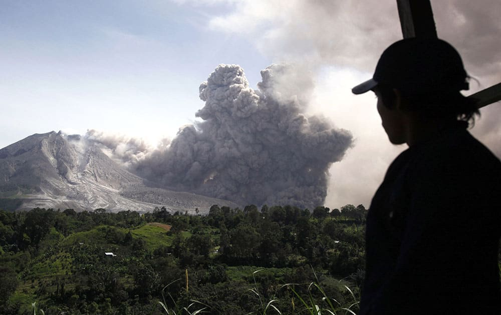 A man watches as Mount Sinabung releases a pyroclastic flow in Tiga Pancur, North Sumatra, Indonesia.