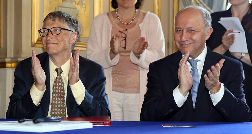 Microsoft co-founder and philanthropist Bill Gates, left, and French Foreign Minister Laurent Fabius, right, applaud after the signature at the Quai d'Orsay in Paris.
