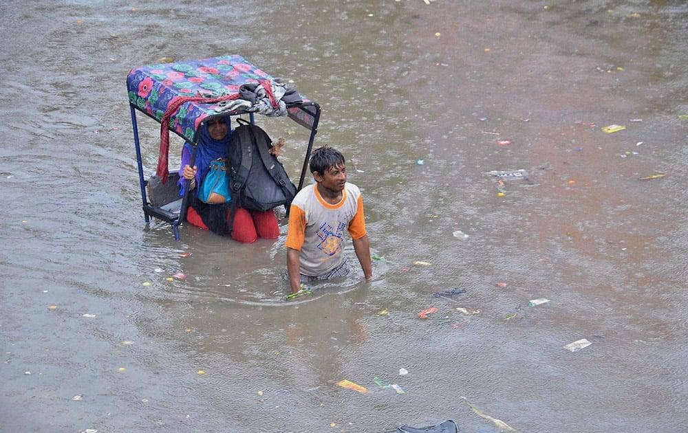 A rickshaw peddler wade through a water logged street after a heavy rains.