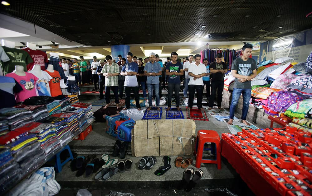 Indonesian Muslim men pray during Friday prayer at a market in Jakarta, Indonesia.