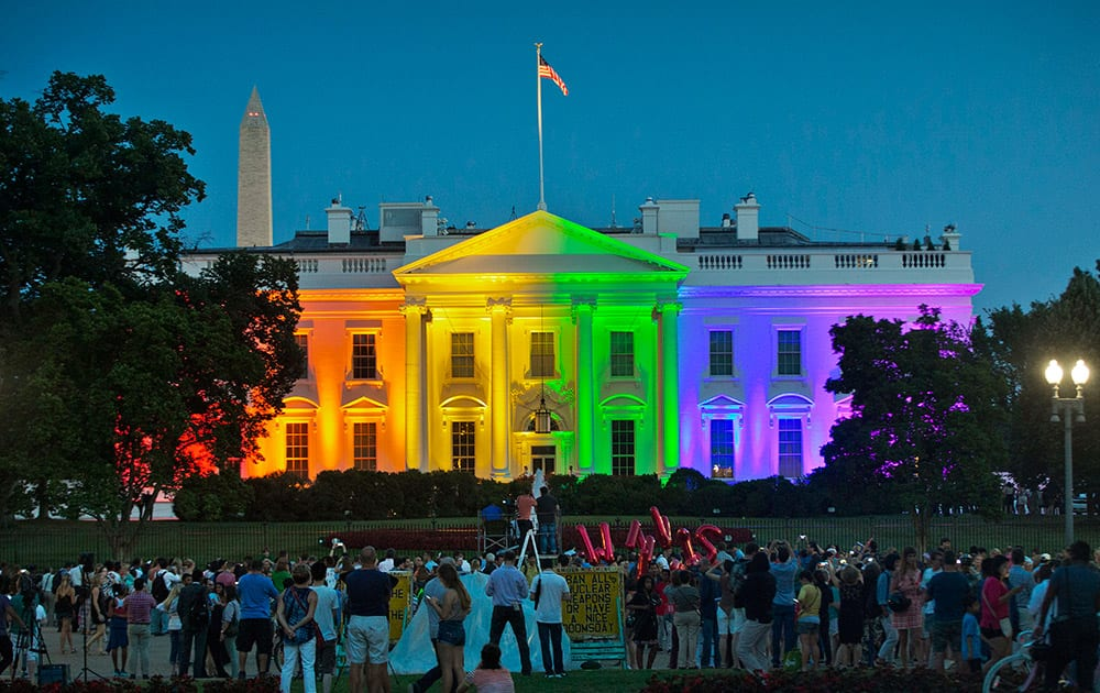 People gather in Lafayette Park to witness the White House being lit up in rainbow colors in commemoration of the Supreme Court's ruling to legalize same-sex marriage, in Washington.