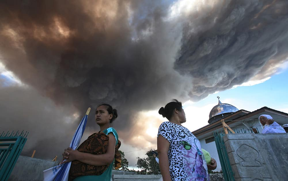 Villagers watch as Mount Sinabung releases volcanic material into the air in Tiga Serangkai, North Sumatra, Indonesia.