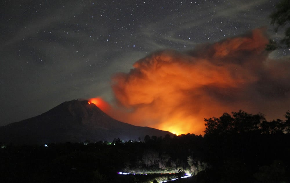Mount Sinabung spews volcanic materials and hot molten lava from its crater as seen from Tiga Pancur, North Sumatra, Indonesia.