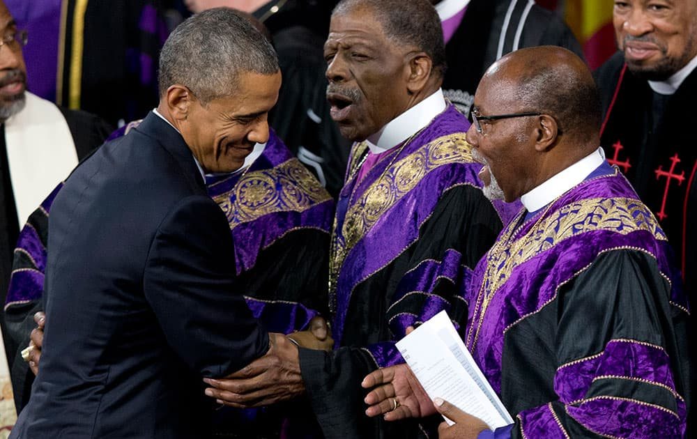 President Barack Obama is greeted by bishops of the Emanuel AME Church as he leaves stage after speaking during services honoring the life of Rev. Clementa Pinckney, in Charleston, S.C., at the College of Charleston TD Arena.