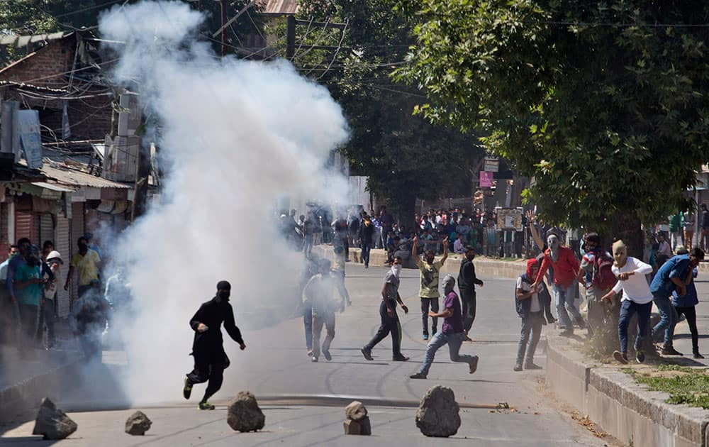 protesters throw stones and bricks at policemen during a protest in Srinagar.