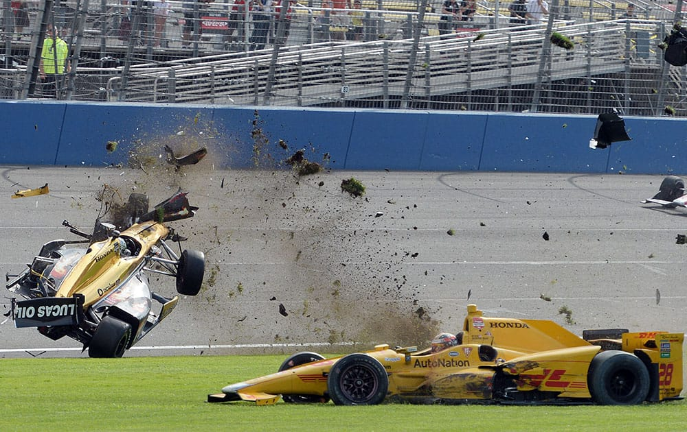Ryan Briscoe, left, flips through the infield grass near Ryan Hunter-Reay, during the IndyCar auto race at Auto Club Speedway in Fontana, Calif.