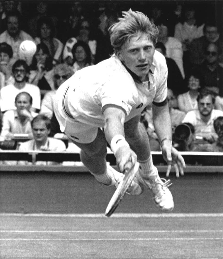 In this July 1, 1985 file photo, Boris Becker, of West Germany, dives to make a return to his opponent Joakim Nystrom, of Sweden, in the men's singles third round play at the All England Lawn Tennis Championships in Wimbledon, London.