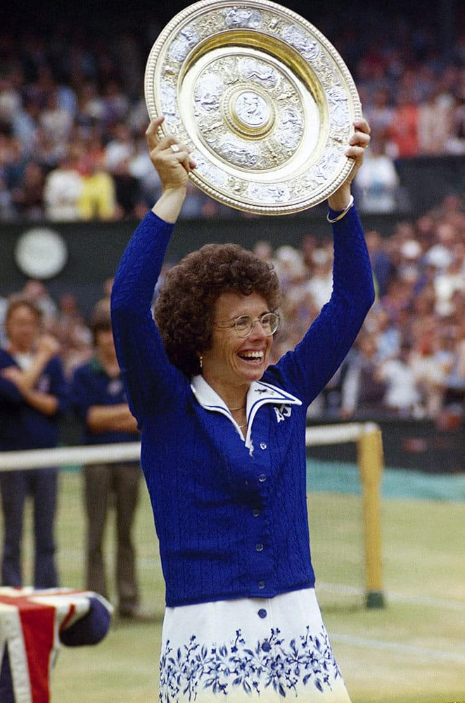 In this July 4, 1975 file photo, U.S. tennis star Billie Jean King holds up the trophy after winning her sixth singles final at the All England Lawn Tennis Championships in Wimbledon, London.