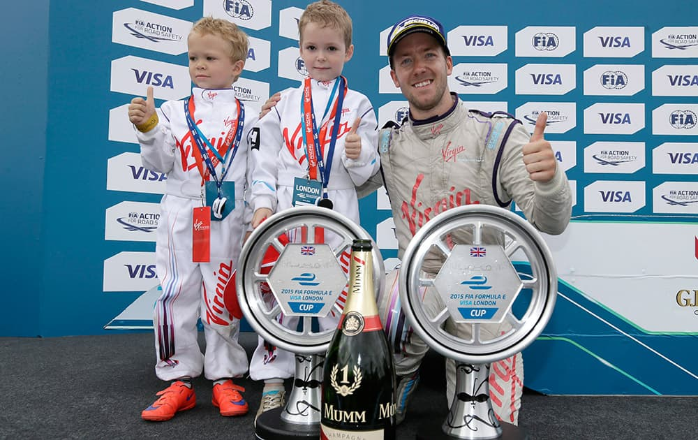 Race winner Britains Sam Bird, driving for Virgin Racing, celebrates with the trophy and his sons, Zak and Flynn, after the Formula E London ePrix auto race in Battersea Park, London.