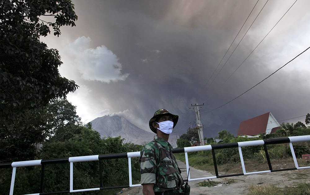 An Indonesian soldier mans a check point on a road leading to the area marked as danger zone on the slopes of Mount Sinabung in Sibintun, North Sumatra, Indonesia.