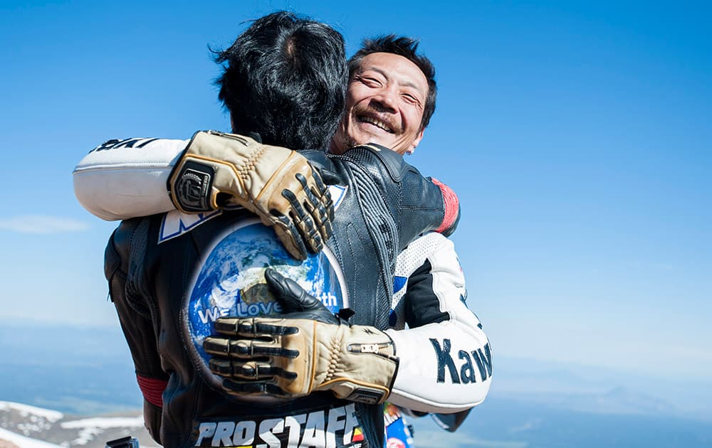 Yoshi Kishimoto, facing camera, is hugged by his friend Yasuo Arai after recording the fastest time for electric-modified motorcycles on top of Pikes Peak during The Broadmoor Pikes Peak International Hill Climb Sunday, June 28 in Cascade, Colo, 2015.