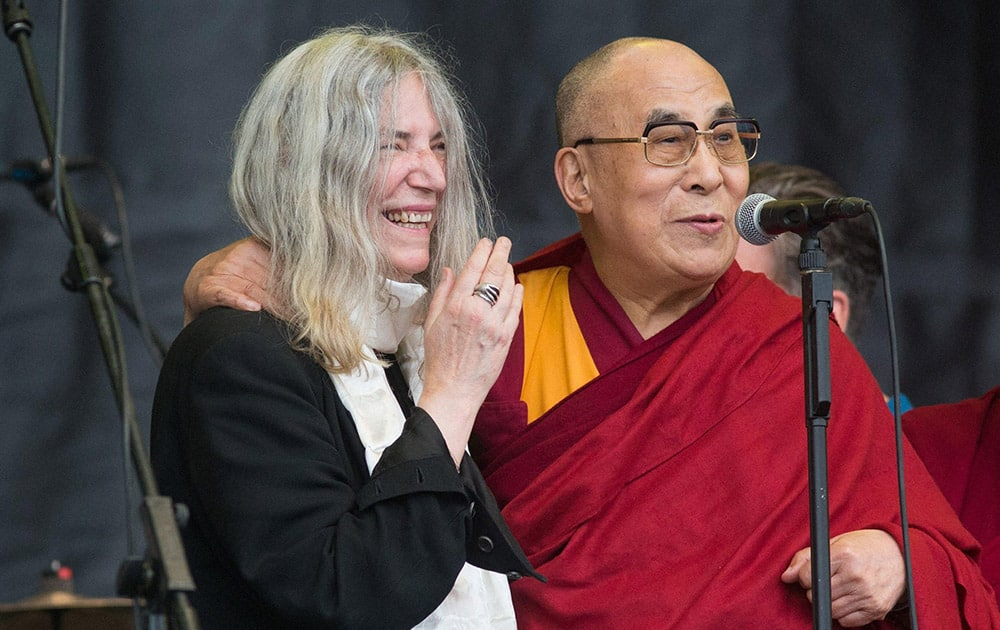 The Dalai Lama speaks to the crowd during singer Patti Smiths, left, performance at the Glastonbury music festival in Glastonbury.