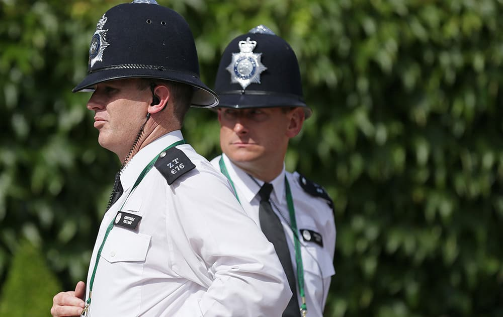 Police officers patrol the grounds before the start of the All England Lawn Tennis Championships in Wimbledon, London.