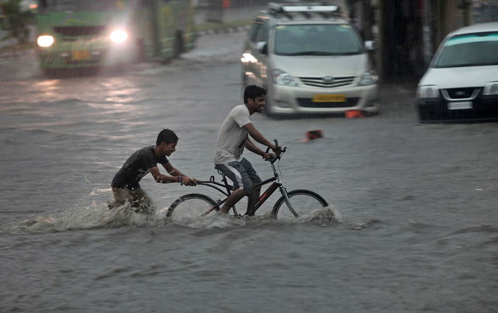 An Indian man pedals a cycle as a boy pushes it through a flooded street during a monsoon shower in Jammu, India.