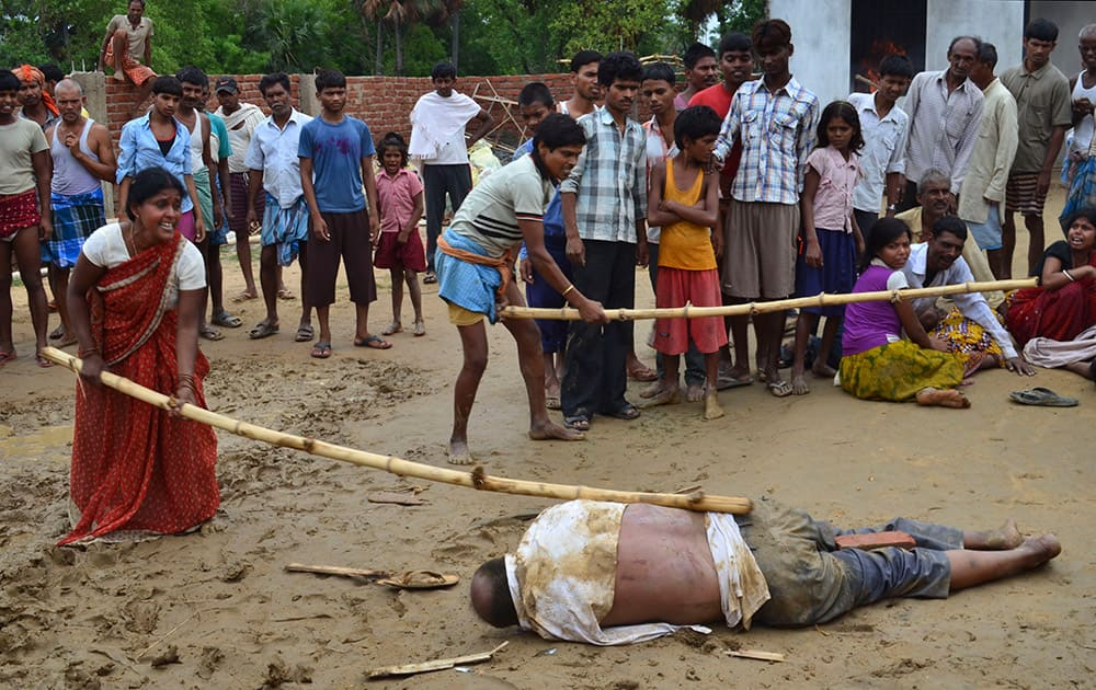 A man and a woman strike the body of a school director with sticks as it lies on the ground in Nirpur village, about 90 kilometers (55 miles) southeast of Patna, the capital of Bihar state, India.