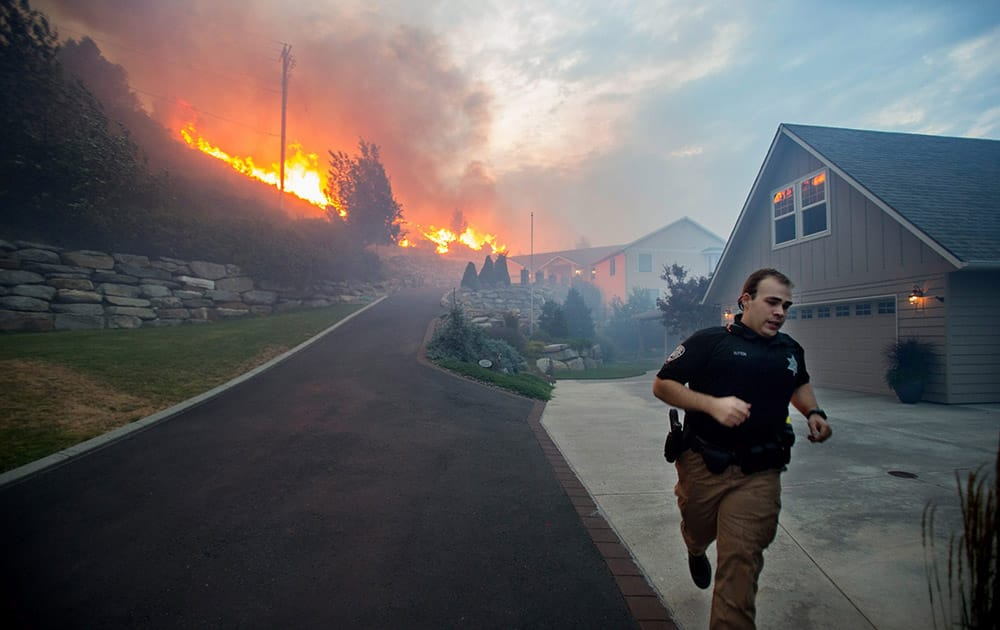 a Chelan County Sheriffs deputy races to check that all residents have left their home as flames approach houses at Quail Hollow Lane in Wenatchee, Wash.