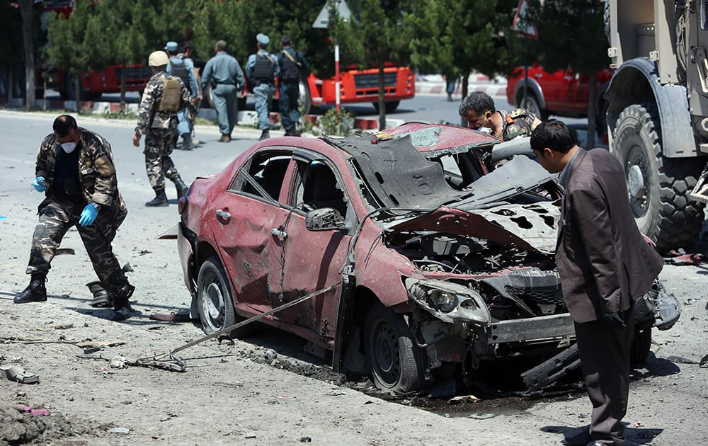 Afghanistan security personnel inspect a destroyed vehicle at the site of a suicide attack on a NATO convoy in Kabul, Afghanistan.