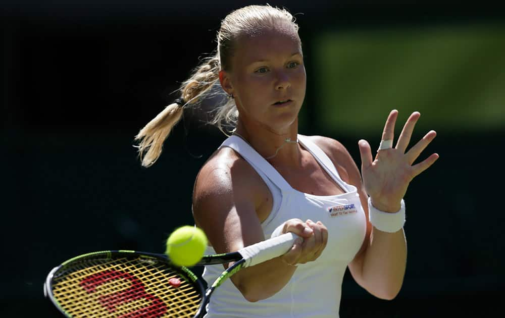 Kiki Bertens of the Netherlands plays a return to Petra Kvitova of the Czech Republic during their singles first round match at the All England Lawn Tennis Championships in Wimbledon, London.