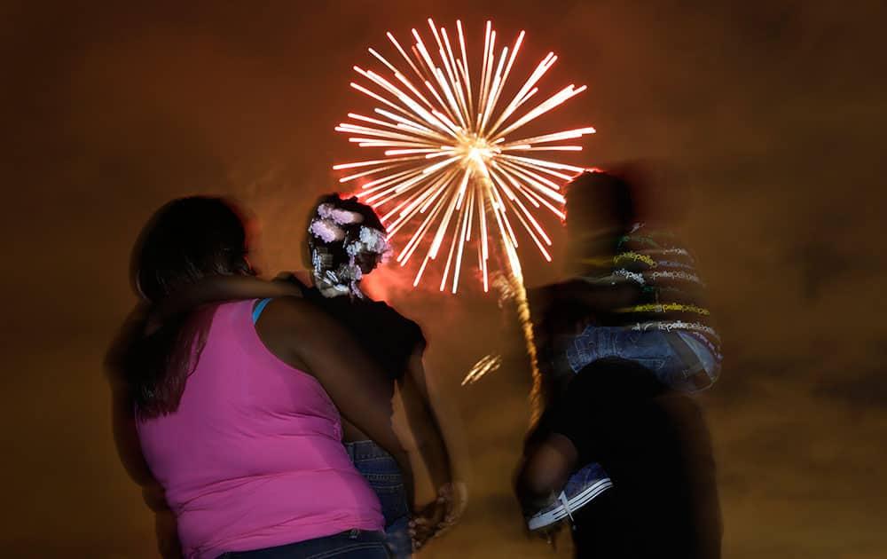People watch a fireworks display in Newark, N.J.