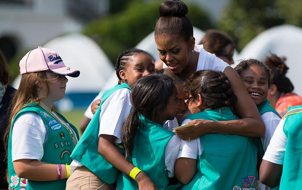 First lady Michelle Obama hugs a group of Girl Scouts during a Lets Move! event on the South Lawn of the White House, in Washington.