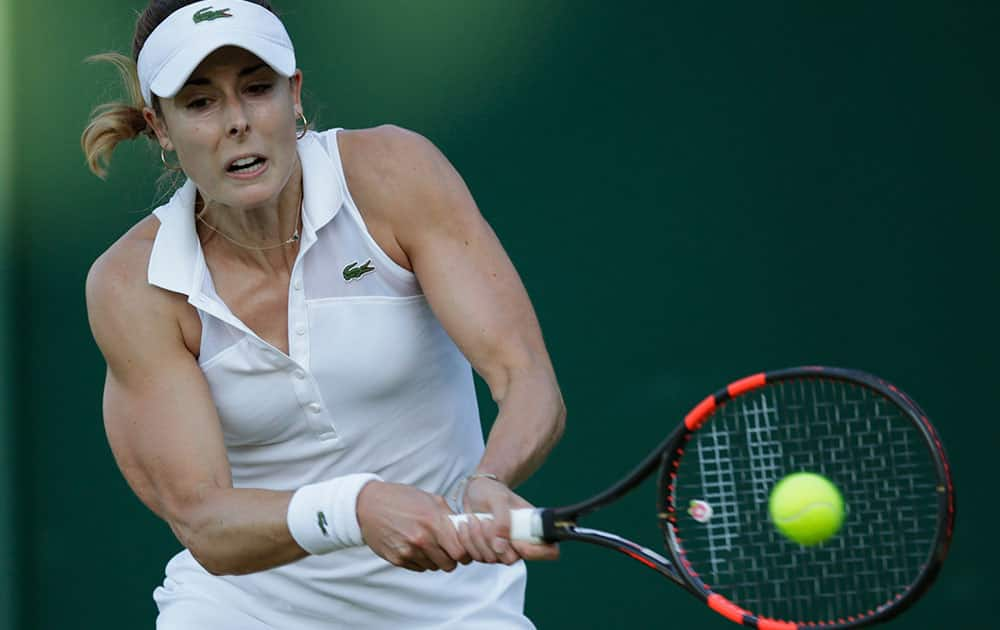 Alize Cornet of France plays a return to Ana Konjuh of Croatia during their women's singles first round match at the All England Lawn Tennis Championships in Wimbledon, London.