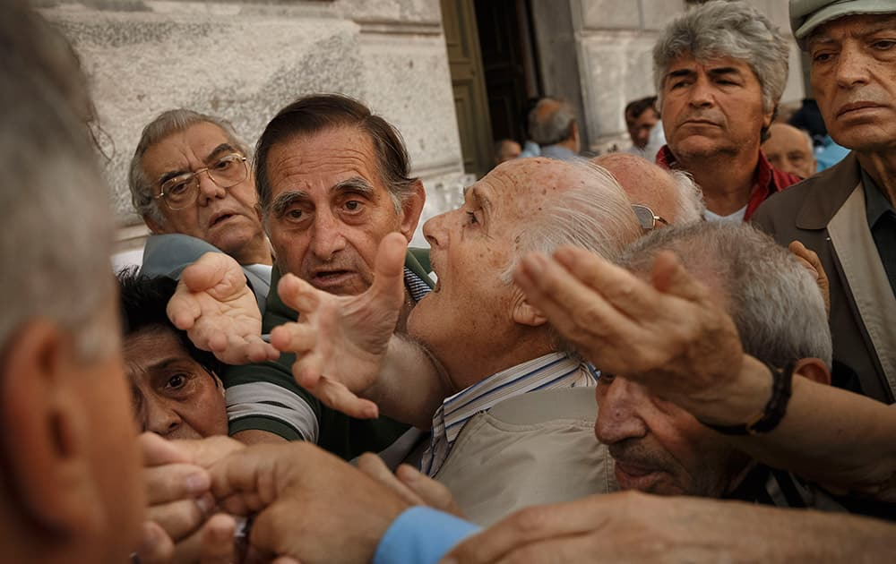 Pensioners try to get a number to enter inside a bank in Athens. About 1,000 bank branches around the country were ordered by the government to reopen Wednesday to help desperate pensioners without ATM cards cash up to 120 euros ($134) from their retirement checks.