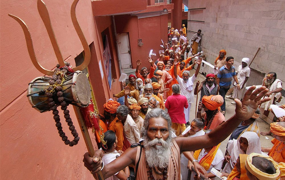 Sadhus stand in a queue to register themselves for the annual pilgrimage to the Amarnath cave shrine at a base camp in Jammu.