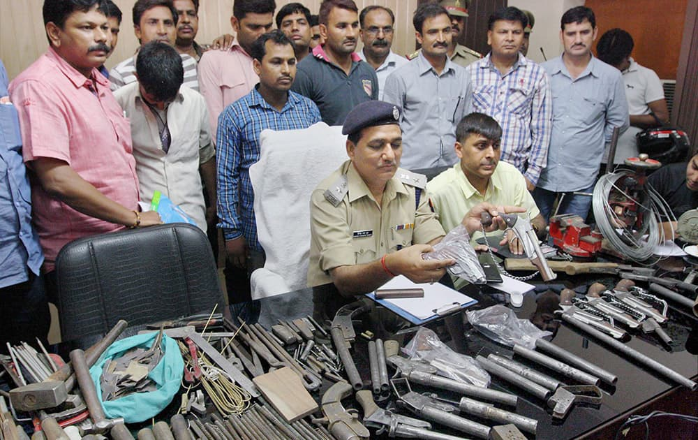 Police officers showing illegal weapons recovered after bust of illegal arms factory in Meerut.