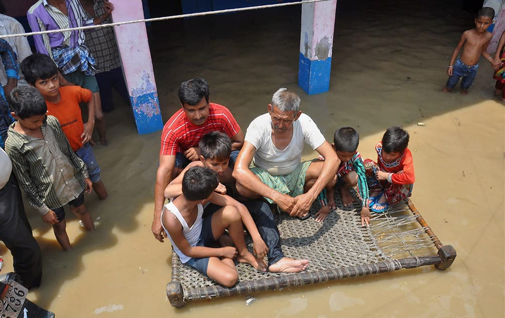 People in a flooded locality in Moradabad district following heavy rain storms.