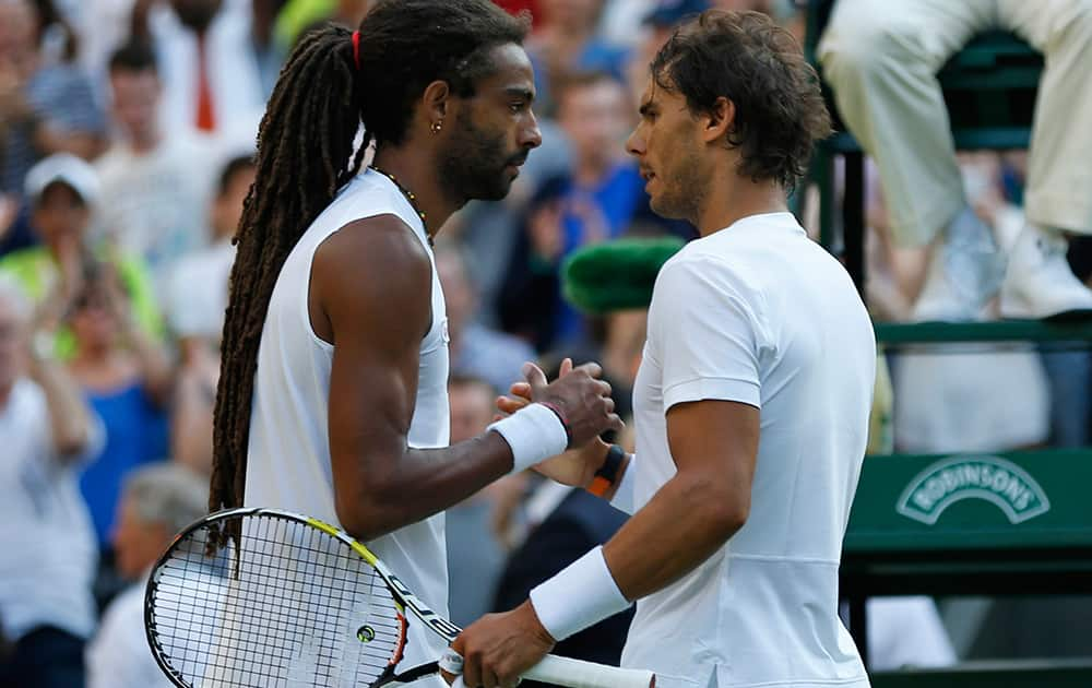 Dustin Brown of Germany shakes hands at the net with Rafael Nadal of Spain, after defeating him during the singles match, at the All England Lawn Tennis Championships in Wimbledon, London.