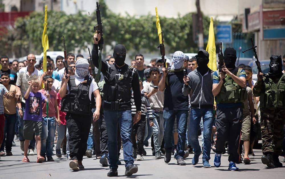 Palestinian gunmen march with their weapons during the funeral of Mohammed Kasbah, 17, who was killed by Israeli forces, during his funeral in the Qalandia refugee camp near the West Bank city of Ramallah.
