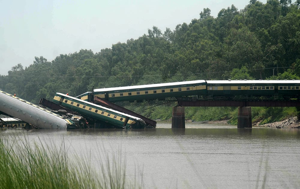 Cars of a passenger train fall after a bridge collapse led a train into a canal in Wazirabad, near Lahore, Pakistan.
