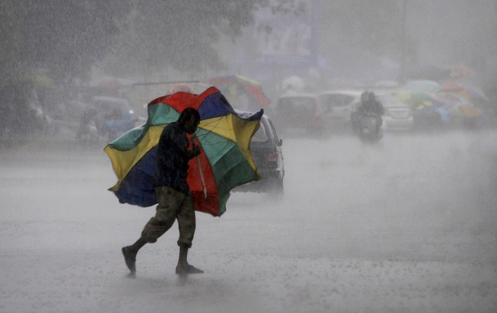 A gust of wind bends the umbrella of a street vendor crossing the road during a heavy downpour in Bhubaneswar.