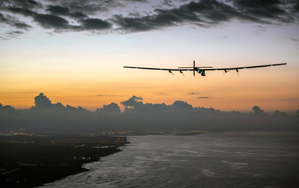 This photo provided by Jean Revillard, Solar Impulse 2, a plane powered by the sun's rays and piloted by Andre Borschberg, approaches Kalaeloa Airport near Honolulu.